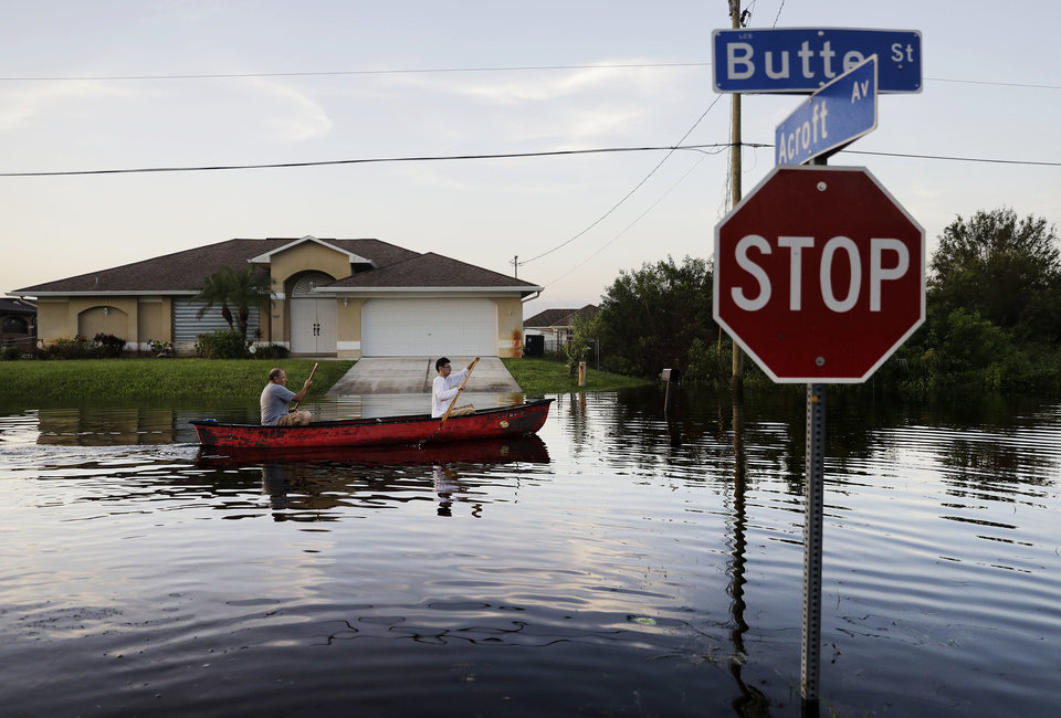 Photo - Pierre Ghantos, left, and his son Nathan paddle though their flooded neighborhood in the aftermath of Hurricane Irma in Fort Myers, Fla., Tuesday, Sept. 12, 2017. (AP Photo/David Goldman)