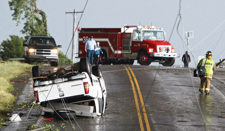 Photo - Power lines cross the road where a truck flipped over as a tornado damaged the area around Interstate 240 and Choctaw Road on Monday in Oklahoma City. Photo by Chris Landsberger, The Oklahoman