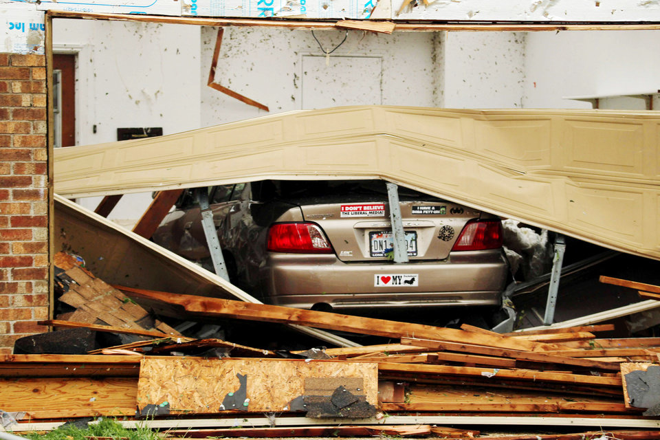 Photo - A car is seen in a damaged home after Wednesday's tornado in Cleburne, Texas on Thursday, May 16, 2013. Ten tornadoes touched down in several small communities in Texas overnight, leaving at least six people dead, dozens injured and hundreds homeless. Emergency responders were still searching for missing people Thursday afternoon. (AP Photo/Ron Russek II)