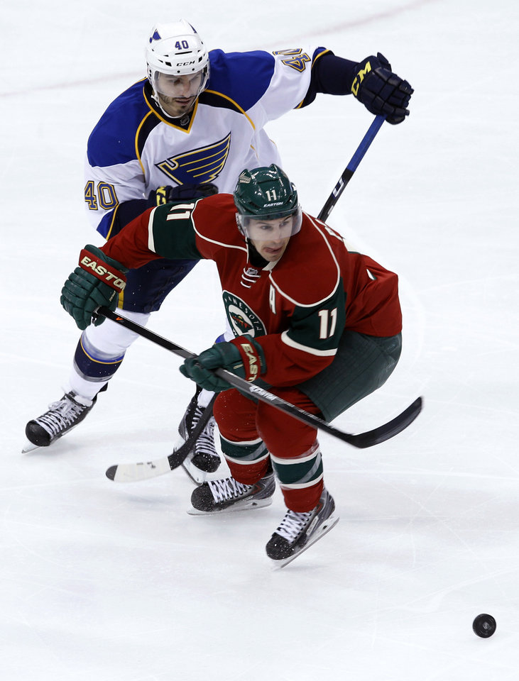 Photo - Minnesota Wild left wing Zach Parise (11) and St. Louis Blues center Maxim Lapierre (40) chase the puck during the first period of an NHL hockey game in St. Paul, Minn., Thursday, April 10, 2014. (AP Photo/Ann Heisenfelt)