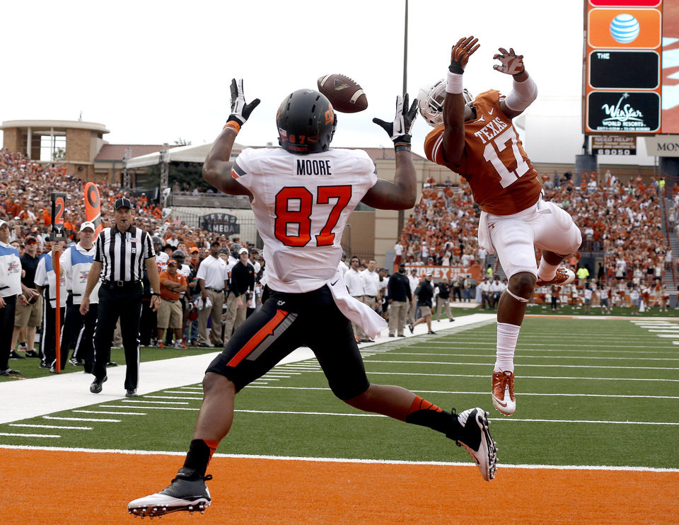Oklahoma State\'s Tracy Moore (87) catches a touchdown pass as UT\'s Adrian Phillips (17) defends in the second quarter a college football game between the Oklahoma State University Cowboys (OSU) and the University of Texas Longhorns (UT) at Darrell K Royal - Texas Memorial Stadium in Austin, Texas, Saturday, Nov. 16, 2013. Photo by Sarah Phipps The Oklahoman