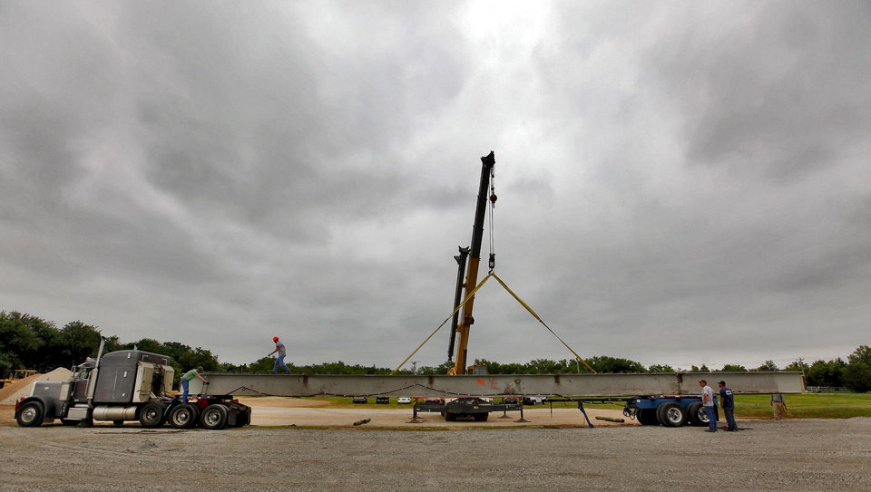 Photo - INTERSTATE 40 / CROSSTOWN EXPRESSWAY / HIGHWAY / BEAMS: Crews work to unload two 20,000-pound steel beams that were the first to be removed from the I-40 crosstown bridge on Monday, May 7, 2012, in Edmond, Oklahoma. The two 90-foot beams will be part of the Deer Creek flood control bridge project on MacArthur near Covell. There will be a total of 1,914 beams removed from I-40 to be repurposed in bridge projects across the state.  Photo by Chris Landsberger, The Oklahoman