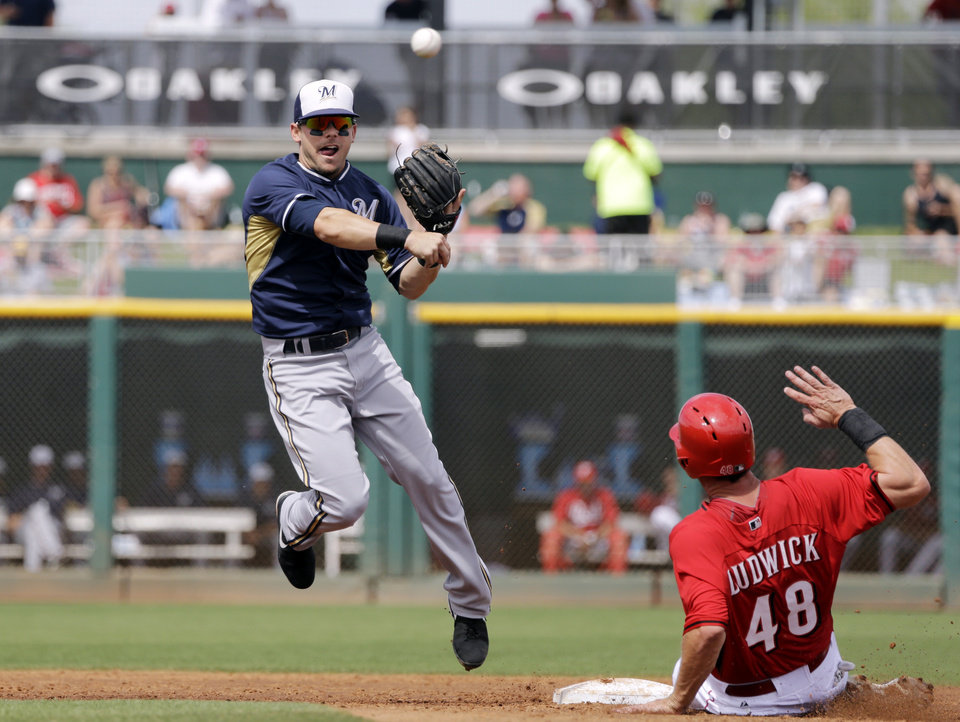 Photo - Milwaukee Brewers second baseman Scooter Gennett, left, throws over Cincinnati Reds' Ryan Ludwick (48) to complete a double play on Reds' Todd Frazier in the second inning of a spring exhibition baseball game Sunday, March 23, 2014, in Goodyear, Ariz. (AP Photo/Mark Duncan)