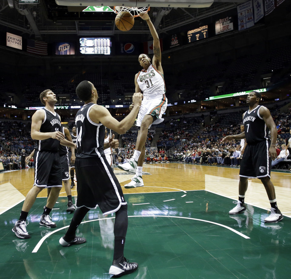 Photo - Milwaukee Bucks' John Henson dunks during the second half of an NBA basketball game against the Brooklyn Nets Saturday, Dec. 7, 2013, in Milwaukee. (AP Photo/Morry Gash)