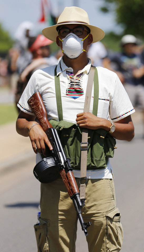Photo - An armed man blocks traffic on NE 23rd in front of the Governor's Mansion at a 1,000 brothers and sisters in arms for second amendment walk by predominantly black men and women to advocate for their second amendment rights, Saturday, June 20, 2020. [Doug Hoke/The Oklahoman]
