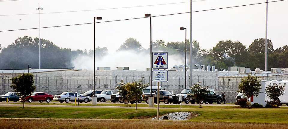 "Smoke rises above the Adams County Correctional Center in Natchez, Miss., Sunday, May 20, 201, during an inmate disturbance at the prison. A guard at the southwest Mississippi prison died Sunday and several other employees were injured during what the facility's private operator is calling ""an inmate disturbance"" that continued into the evening. (AP Photos/The Natchez Democrat, Lauren Wood)"