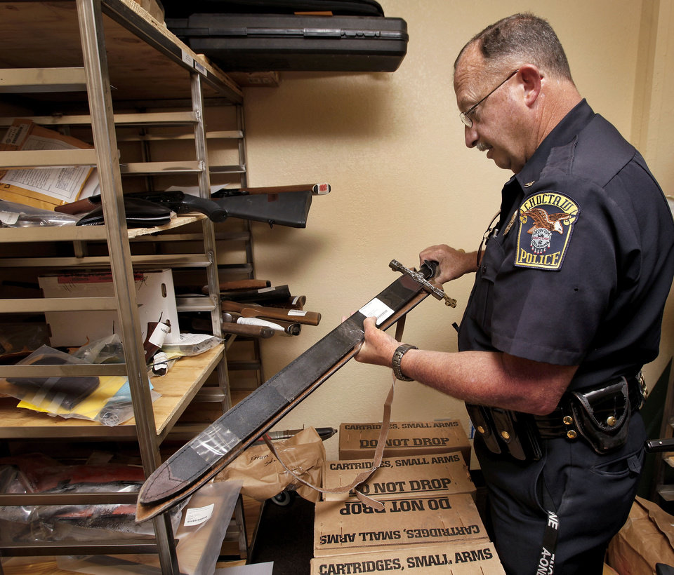Choctaw Police Chief Conny Clay unsheaths a sword in the property room at the Choctaw Police Department on Thursday, July 26, 2012.  Photo by Jim Beckel, The Oklahoman. <strong>Jim Beckel - THE OKLAHOMAN</strong>