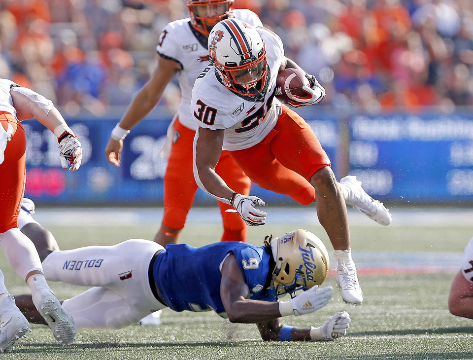 Photo - Oklahoma State's Chuba Hubbard (30) is tripped up by Tulsa's Reggie Robinson II (9) during a college football game between the Oklahoma State University Cowboys (OSU) and the University of Tulsa Golden Hurricane (TU) at H.A. Chapman Stadium in Tulsa, Okla., Saturday, Sept. 14, 2019. [Sarah Phipps/The Oklahoman]