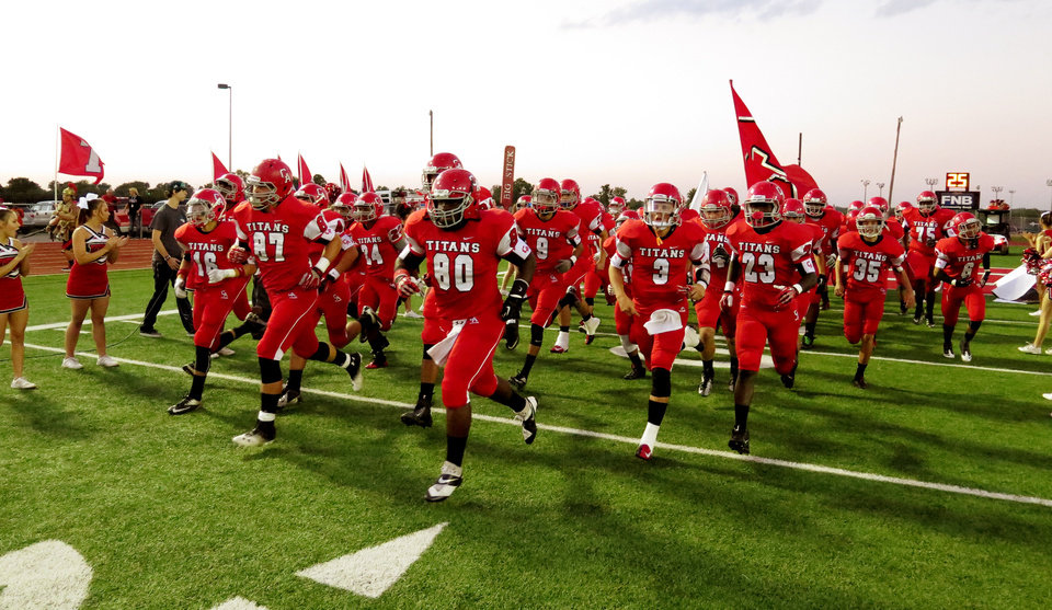 Photo - The Carl Albert Titans come onto the field during the high school football game between Guthrie at Carl Albert in Midwest City, Friday, October 11, 2013.  Photo by Doug Hoke, The Oklahoman