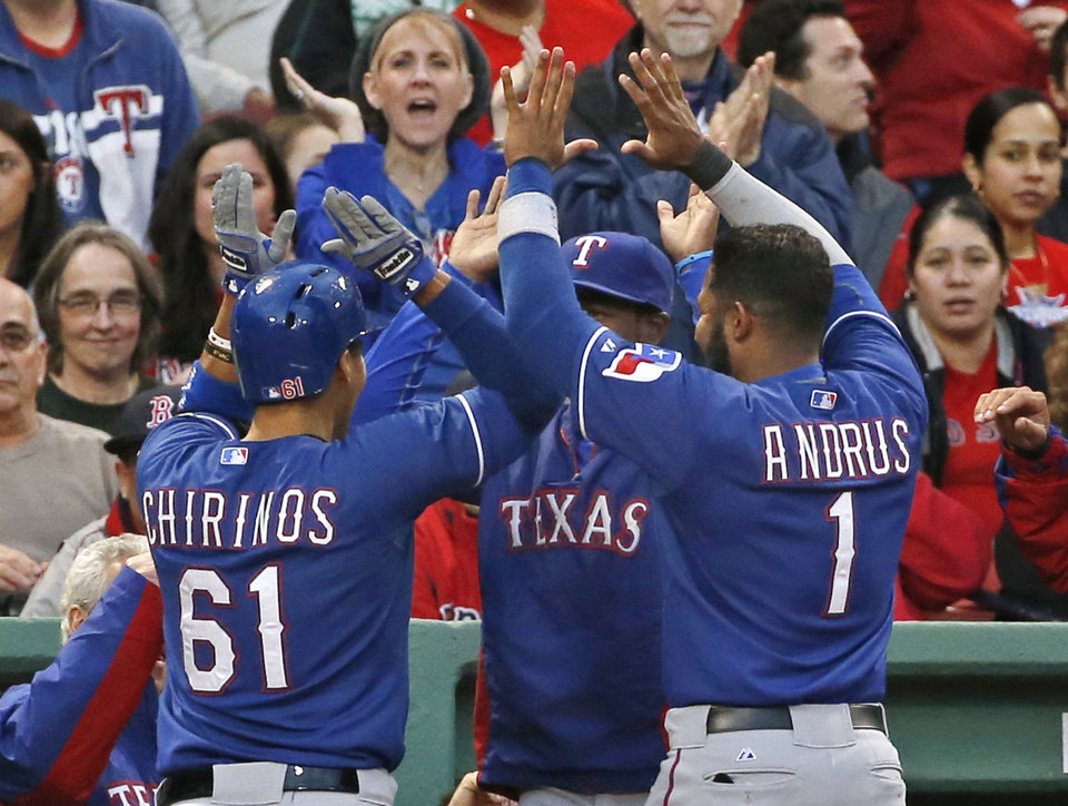 Photo - Texas Rangers' Robinson Chirinos (61) celebrates his solo home run with teammates at the dugout in the third inning of a baseball game against the Boston Red Sox at Fenway Park in Boston, Tuesday, April 8, 2014. (AP Photo/Elise Amendola)