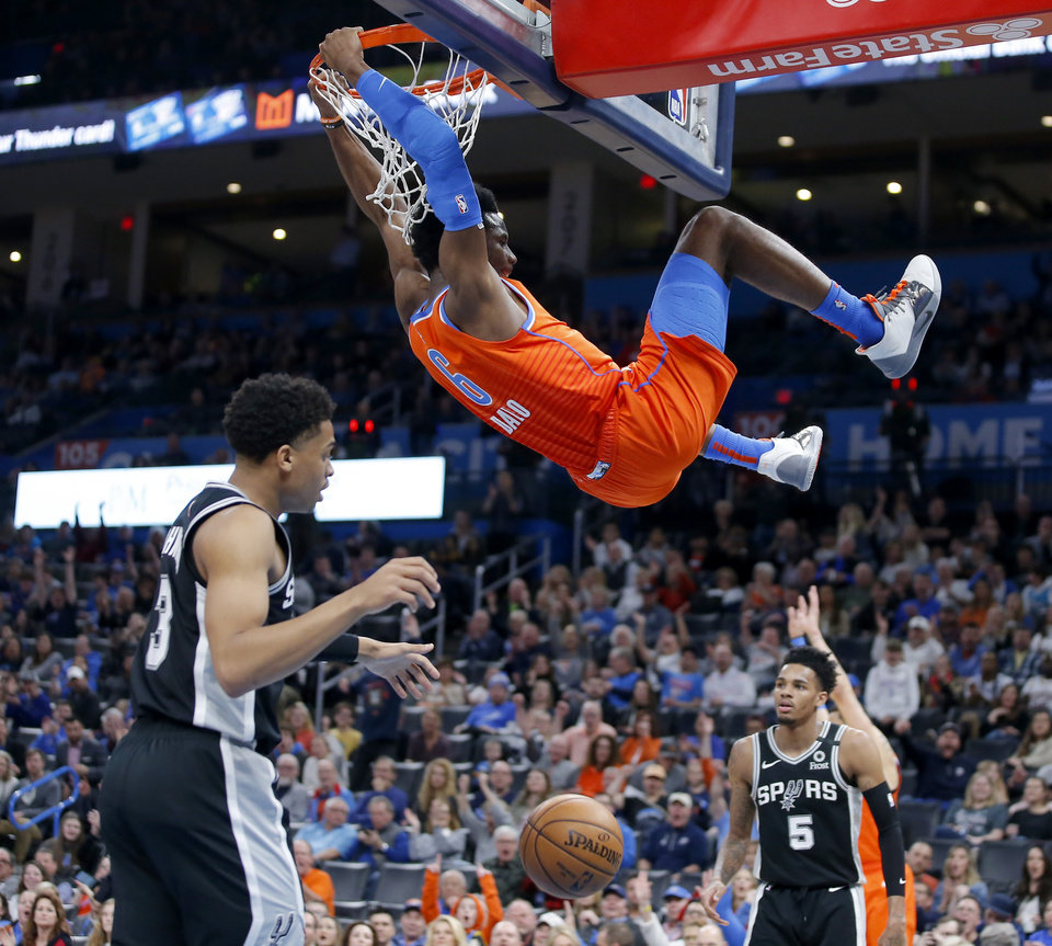Photo - Oklahoma City's Hamidou Diallo (6) dunks the ball between San Antonio's Keldon Johnson (3) and Dejounte Murray (5) during an NBA basketball game between the Oklahoma City Thunder and the San Antonio Spurs at Chesapeake Energy Arena in Oklahoma City, Sunday, Feb. 23, 2020. Oklahoma city won 131-103. [Bryan Terry/The Oklahoman]