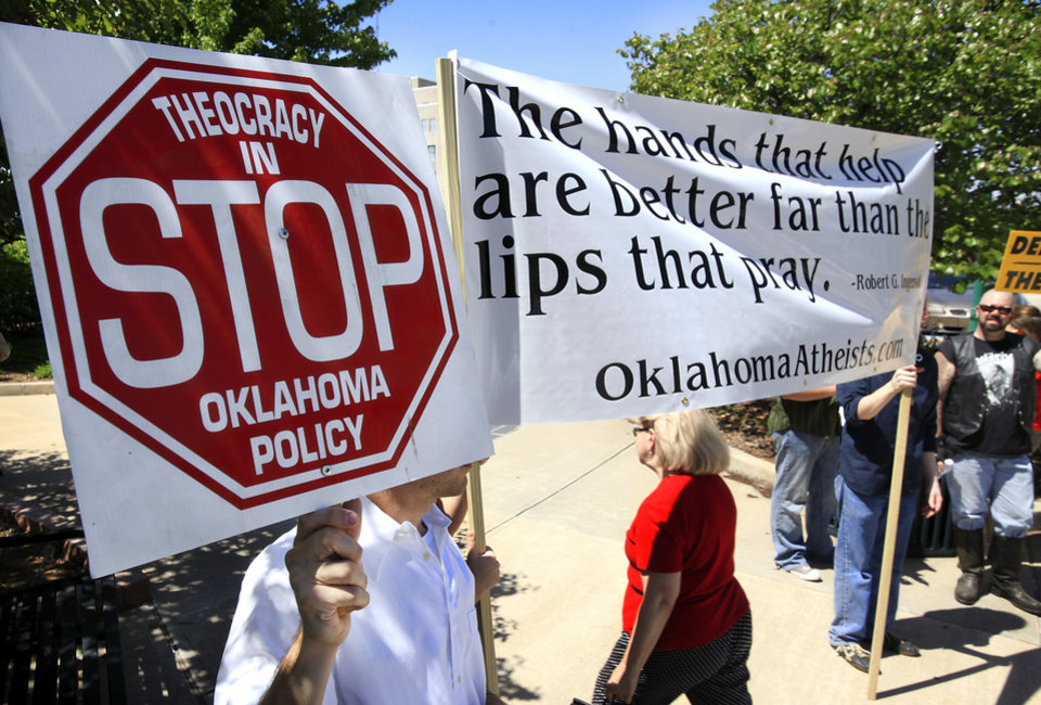 Photo - Less than a dozen people representing Oklahoma Atheists stood across the street from the prayer group to voice opposition to what they called