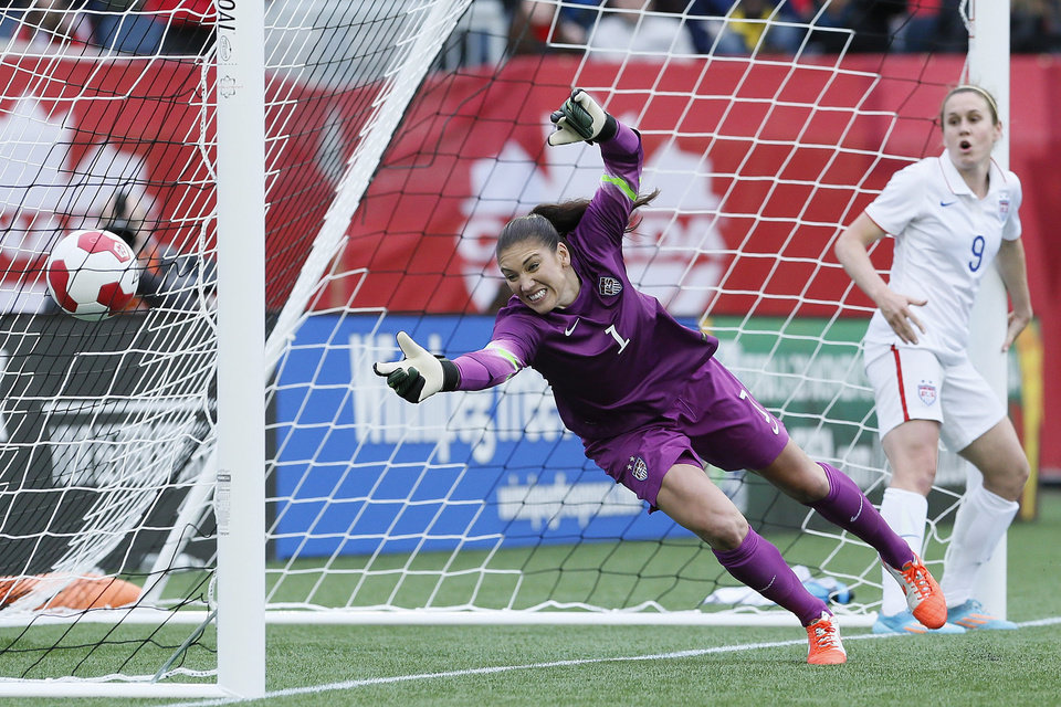 Photo - As USA's midfielder Heather O'Reilly (9) looks on goalkeeper Hope Solo (1) can't stop the header from Canada's defender Kadeisha Buchanan (20) during first half soccer action of a friendly match in Winnipeg, Manitoba, Thursday, May 8, 2014. (AP Photo/The Canadian Press, John Woods)