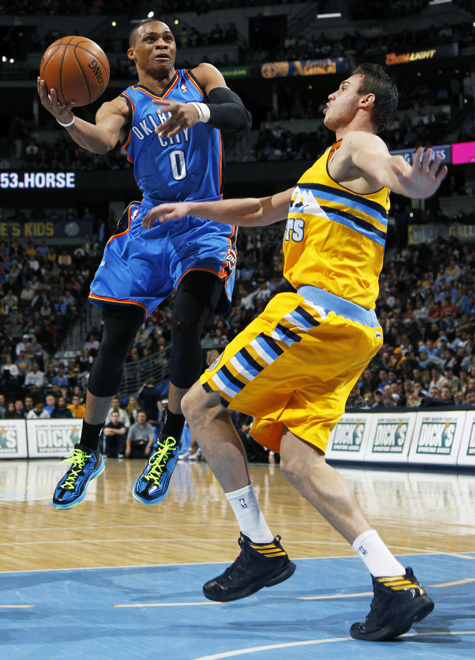 Oklahoma City Thunder guard Russell Westbrook, left, drives the lane for a shot against Denver Nuggets forward Danilo Gallinari, of Italy, in the first quarter of an NBA basketball game in Denver on Sunday, Jan. 20, 2013. (AP Photo/David Zalubowski)
