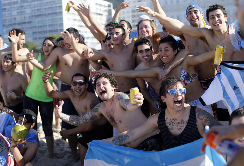 Photo - Argentina soccer fans cheer on Copacabana beach the morning of the final World Cup match between Argentina and Germany in Rio de Janeiro, Brazil, Sunday, July 13, 2014. (AP Photo/Silvia Izquierdo)
