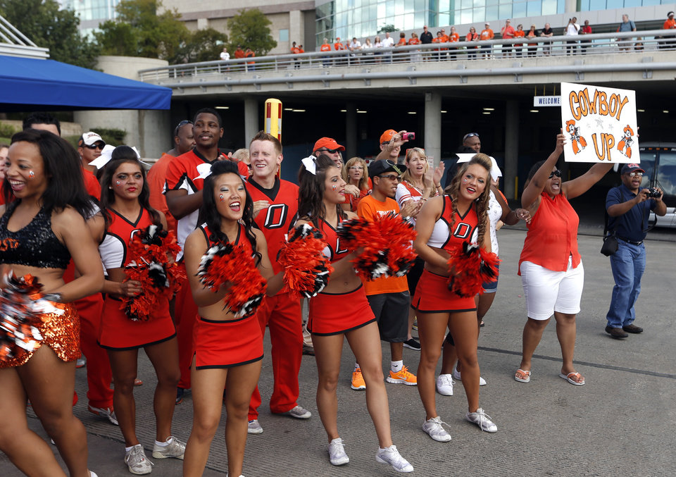 Photo - Oklahoma State fans and cheerleaders cheer on the Cowboys during the walk before the college football game between the University of Texas at San Antonio Roadrunners (UTSA) and the Oklahoma State University Cowboys (OSU) at the Alamodome in San Antonio, Saturday, Sept. 7, 2013.  Photo by Sarah Phipps, The Oklahoman