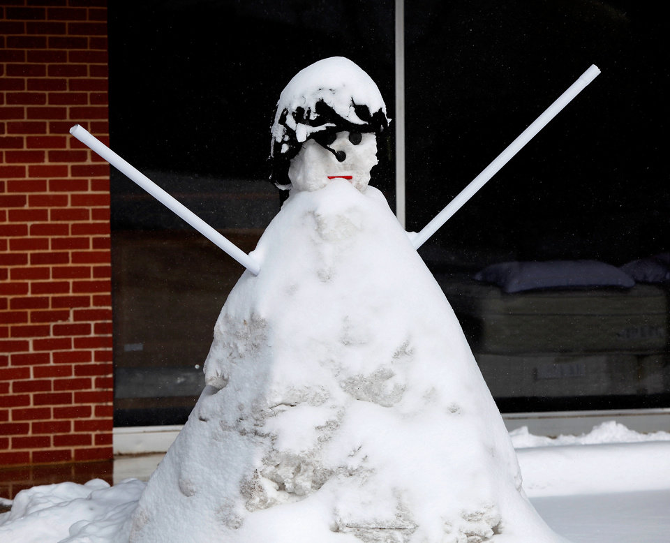 Photo - A snowman in front of a business on SE 29 Street in Del City. It was built by shop owner Raul Espinosa. A second winter storm in a week dumped about 6 inches of snow in the Oklahoma City area Tuesday morning, Feb. 9, 2011.   Photo by Jim Beckel, The Oklahoman