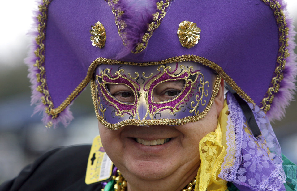 Photo - Mike Ernst smiles while decked out in his Mardi Gras best Sunday, Feb. 10, 2013 at the St. Paul's Carnival Association Parade in Pass Christian, Miss. (AP Photo/The Sun Herald, Tim Isbell)
