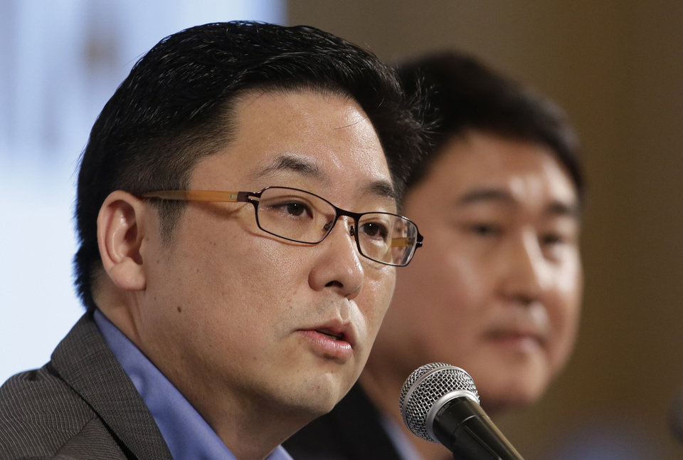 Photo - Daum Communications Corp. CEO Choi Sae-hoon, left, answers a reporter's question as Kakao Corp. CEO Sirgoo Lee listens during their press conference in Seoul, South Korea, Monday, May 26, 2014. Mobile messenger service Kakao Talk is seeking a backdoor listing on the South Korean stock exchange by combining with the country's second largest Internet portal. (AP Photo/Lee Jin-man)
