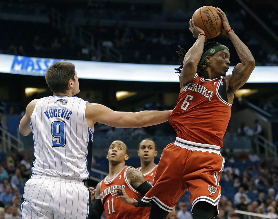 Photo - Milwaukee Bucks' Marquis Daniels (6) looks to pass the ball as he is guarded by Orlando Magic's Nikola Vucevic (9), of Montenegro, during the first half of an NBA basketball game, Wednesday, April 10, 2013, in Orlando, Fla. (AP Photo/John Raoux)