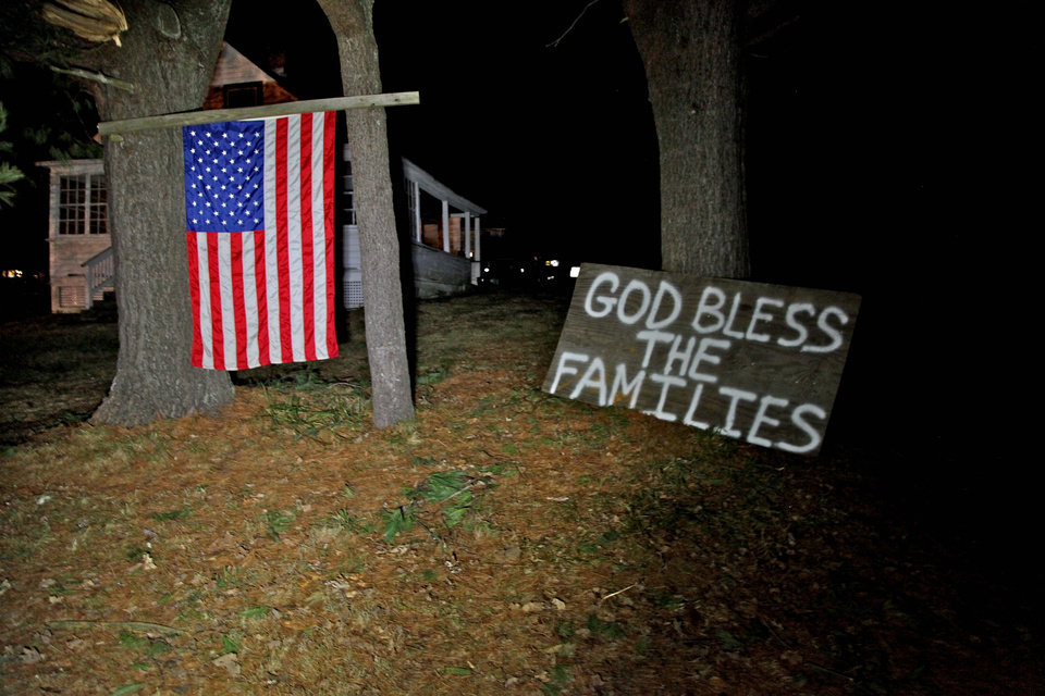 Photo - Across the street from the elementary school in Sandy Hook, Conn. neighbors hoisted an American flag and created a make-shift prayer for the deceased inside the school late Friday Dec. 14, 2012. (AP Photo/Robert Ray)