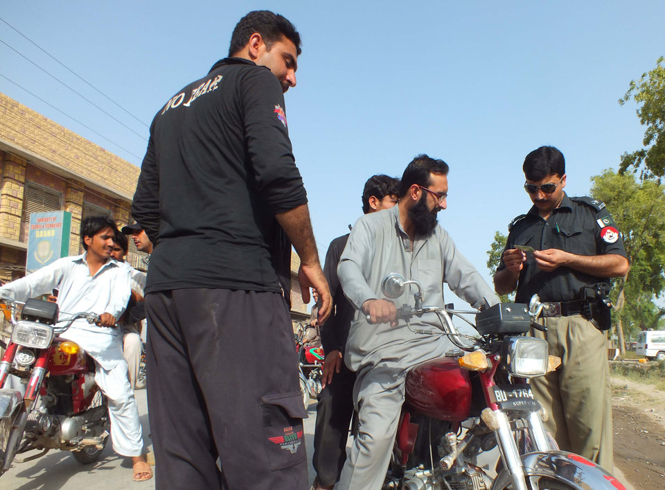 Photo - Pakistani police officers check identities of motorcyclists in Bannu near the tribal area of North Waziristan, Monday, June 16, 2014 in Pakistan. Pakistan's air force pounded targets in the country's northwest Monday, killing 27 militants, officials said, as the government finally pushed ahead with a military offensive against insurgent safe havens. (AP Photo/Ijaz Muhammad)