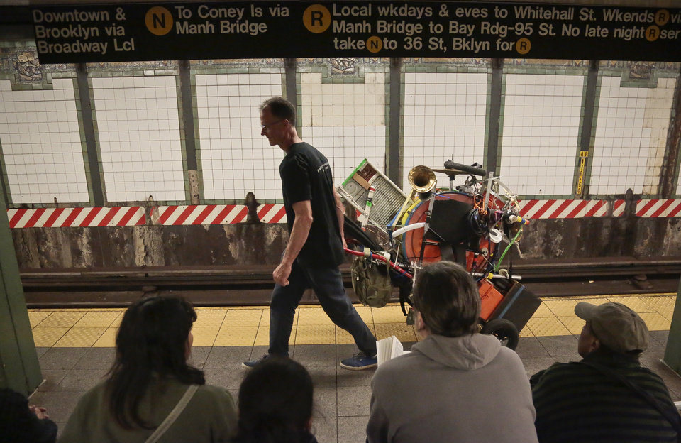Photo - In this Wednesday, Oct. 9, 2013, photo, Jeffrey Masin pulls his one-man band ensemble along a subway platform in New York.  Masin, from Waterford, Conn., has performed his one-man band show he calls
