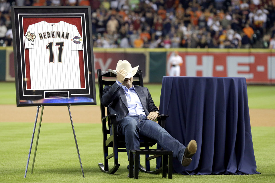 Photo - Former Houston Astros player Lance Berkman sits back in his rocking chair during a ceremony to recognize his contributions to the team before a baseball game against the Los Angeles Angels, Saturday, April 5, 2014, in Houston. Berkman and former teammate Roy Oswalt signed one-day personal services contracts so they could retire as Astros. Each received a World Series jersey, a Stetson and a personalized rocking chair. (AP Photo/Pat Sullivan)