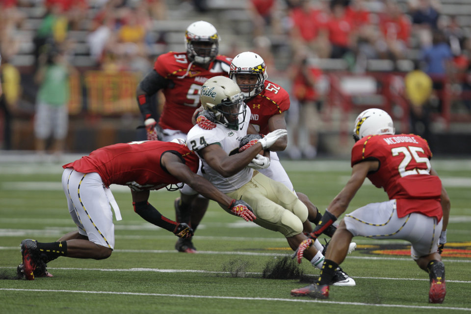 Photo -   William & Mary's Keith McBride (24) runs the ball as Maryland's Jeremiah Johnson, left, Darin Drakeford (52) and Dexter McDougle (25) defend during the second half of a NCAA college football game, Saturday, Sept. 1, 2012, in College Park, Md. Maryland won 7-6. (AP Photo/Luis M. Alvarez)
