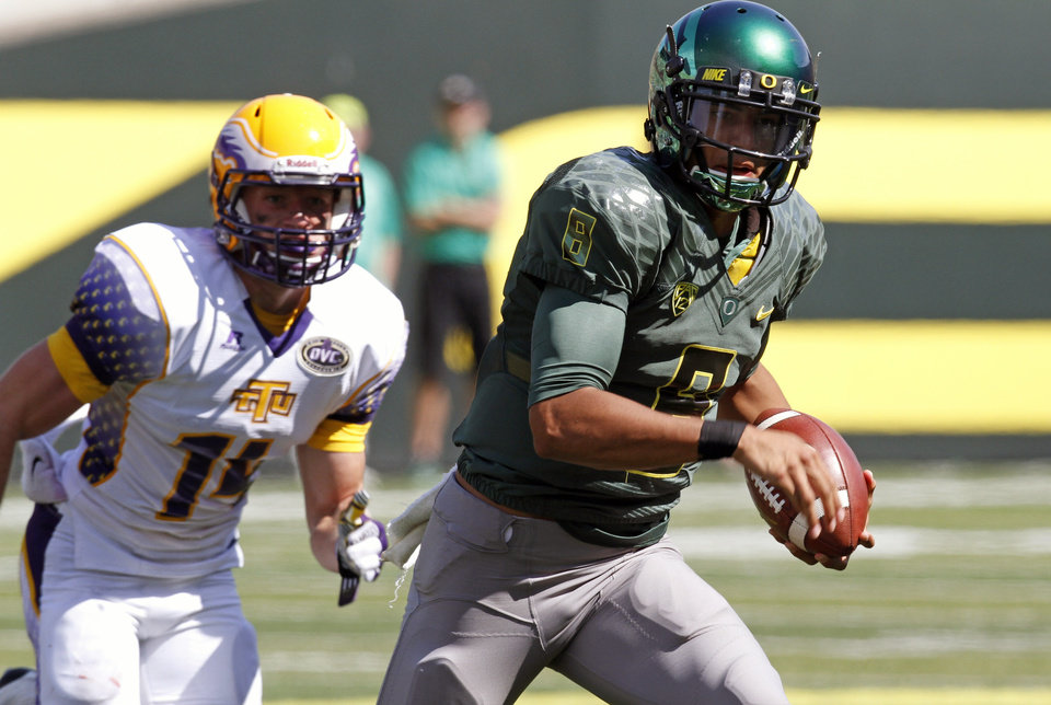 Photo -   Oregon quarterback Marcus Mariota, right, gains yardage against Tennessee Tech defender Austin Tallant during the first half of their NCAA college football game in Eugene, Ore., Saturday, Sept. 15, 2012. (AP Photo/Don Ryan)