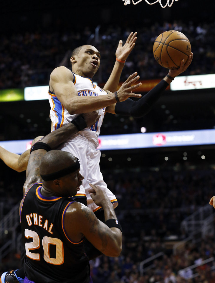 Photo - Oklahoma City Thunder's Russell Westbrook, top, gets fouled by Phoenix Suns' Jermaine O'Neal (20) as he goes up for a shot during the first half in an NBA basketball game Sunday, Feb. 10, 2013, in Phoenix.(AP Photo/Ross D. Franklin)