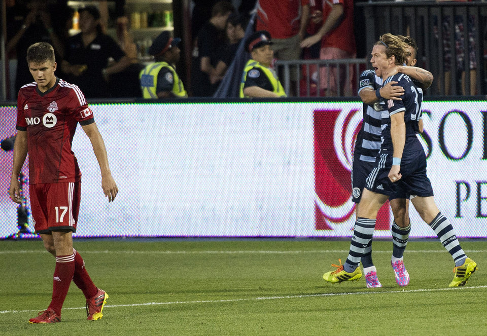 Photo - Sporting Kansas City forward Jacob Peterson, right, celebrates his soccer game-winning goal as Toronto FC defender Nick Hagglund, left, walks past during second-half MLS action in Toronto, Saturday, July 26, 2014. (AP Photo/The Canadian Press, Nathan Denette)