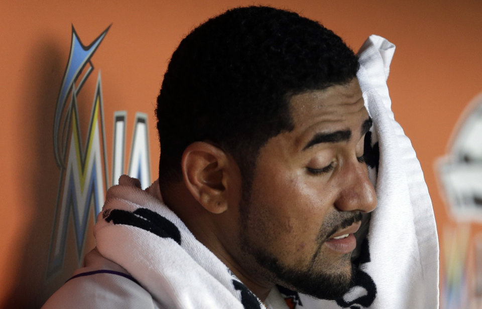 Photo - Colorado Rockies starting pitcher Franklin Morales wipes his face with a towel in the dugout before pitching in the first inning of a baseball game against the Miami Marlins, Thursday, April 3, 2014, in Miami. (AP Photo/Lynne Sladky)