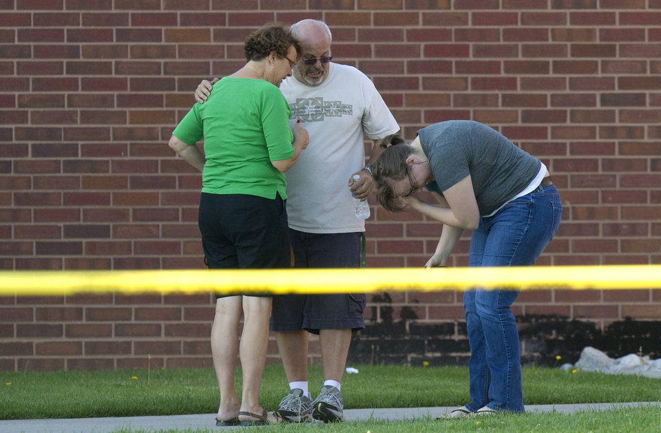 Photo - Tom Sullivan, center, stands with family members outside Gateway High School where witness were brought for questioning after a gunman opened fire at the midnight premiere of The Dark Knight Rises Batman movie Friday, July 20, 2012 in Aurora, Colo. Sullivan later pleaded with the media to help find his missing son, Alex Sullivan, who attended the movie to celebrate his 27th birthday.   A gunman wearing a gas mask set off an unknown gas and fired into the crowded movie theater killing 12 people and injuring at least 50 others, authorities said. (AP Photo/Barry Gutierrez) ORG XMIT: COBG116