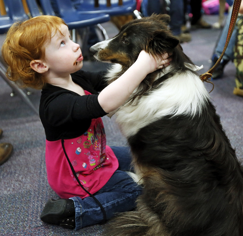 Lillie Cowsert, 2, pets Josey, a therapy dog from Ardmore, Okla., with Therapy Dogs International, during a meet and greet with teachers and students from Plaza Towers Elementary at Eastlake Elementary School in Oklahoma City, Thursday, May 23, 2013. Seven Plaza Towers students died when a tornado destroyed the school in Moore, Okla., on Monday. Cowsert\'s older brother, Brett Cowsert, 7, is a 1st-grader at Plaza Towers. Photo by Nate Billings, The Oklahoman