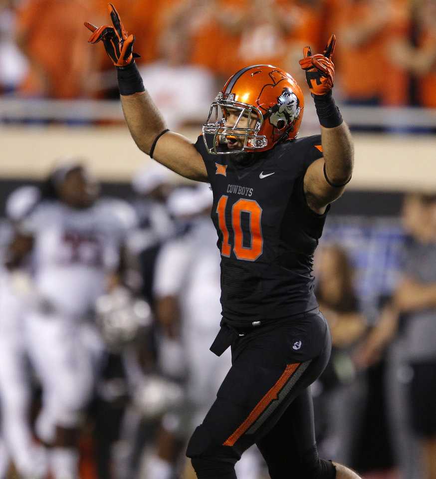 Photo - Oklahoma State's Seth Jacobs (10) celebrates after an interception during a college football game between the Oklahoma State Cowboys (OSU) and the Texas Tech Red Raiders at Boone Pickens Stadium in Stillwater, Okla., Thursday, Sept. 25, 2014. Photo by Bryan Terry, The Oklahoman