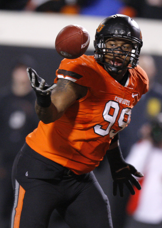 Photo - Oklahoma State's Richetti Jones (99) recovers a fumble during the Bedlam college football game between the Oklahoma State University Cowboys (OSU) and the University of Oklahoma Sooners (OU) at Boone Pickens Stadium in Stillwater, Okla., Saturday, Dec. 3, 2011. Photo by Bryan Terry, The Oklahoman