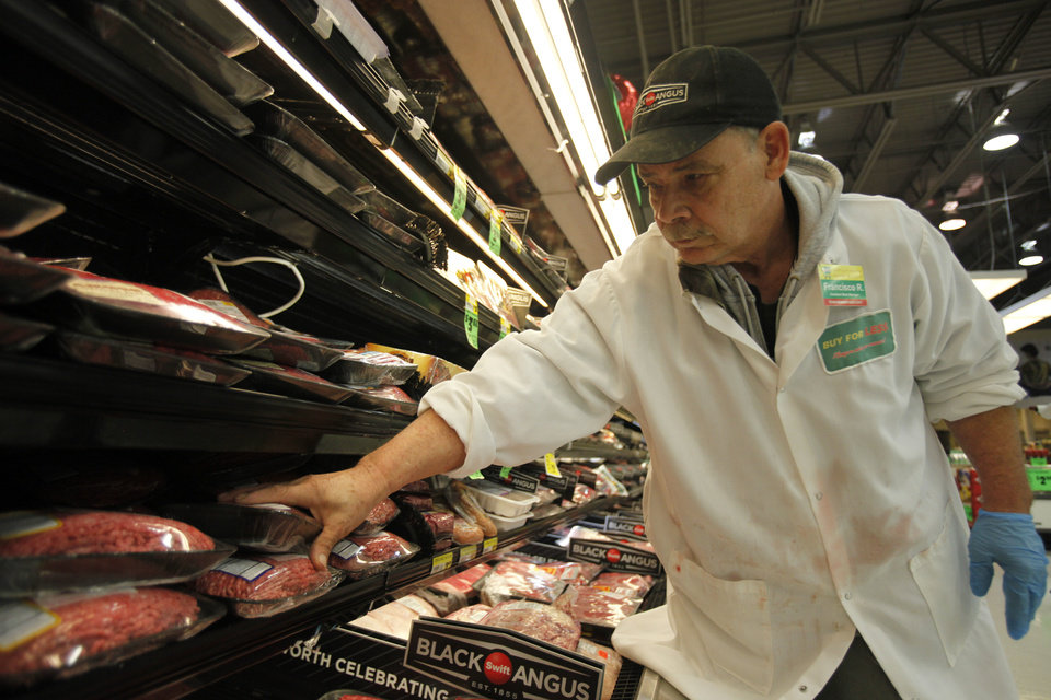 Photo - Francisco Ramirez, assistant meat manager, stocks the meat department at Buy For Less on NW Expressway.  Aliki Dyer - The Oklahoman