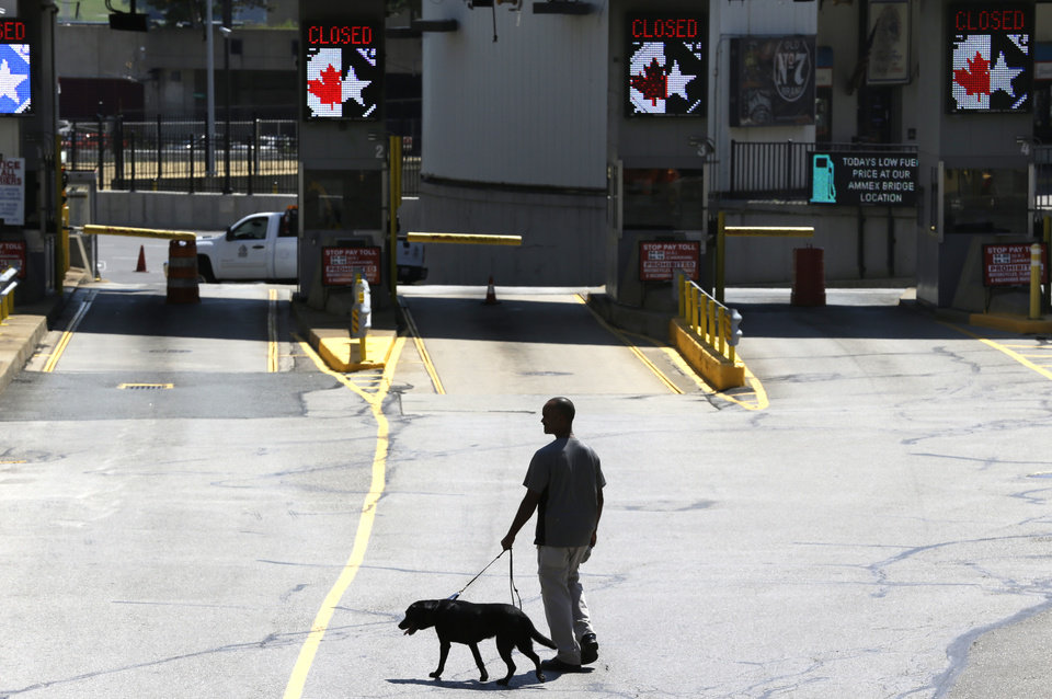 Photo -   A dog is used by authorities to investigate a bomb threat at the Detroit Windsor Tunnel Thursday, July 12, 2012. The tunnel was closed to traffic after the threat was called in on the Canadian side, tunnel chief executive Neal Belitsky told The Associated Press. The call was made some time after 12:30 p.m. to the duty free shop on a plaza on the tunnel's Windsor side, tunnel executive vice president Carolyn Brown said. The underwater tunnel stretches about a mile beneath the Detroit River, which is one of North America's busiest trade crossings. (AP Photo/Paul Sancya)