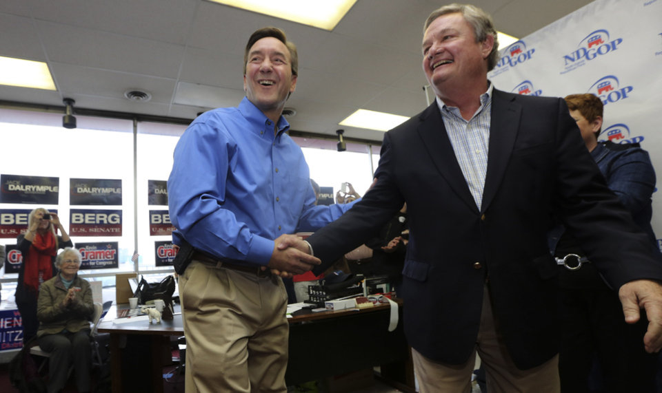 Governor of North Dakota Jack Dalrymple, right, shakes hands with Republican U.S. Senate candidate Rick Berg after an introduction at the NDGOP Victory Office during a campaign stop in Grand Forks, N.D, Sunday, Nov. 4, 2012. Berg is running against Democrat Heidi Heitkamp for North Dakota's U.S Senate seat. (AP Photo/LM Otero)