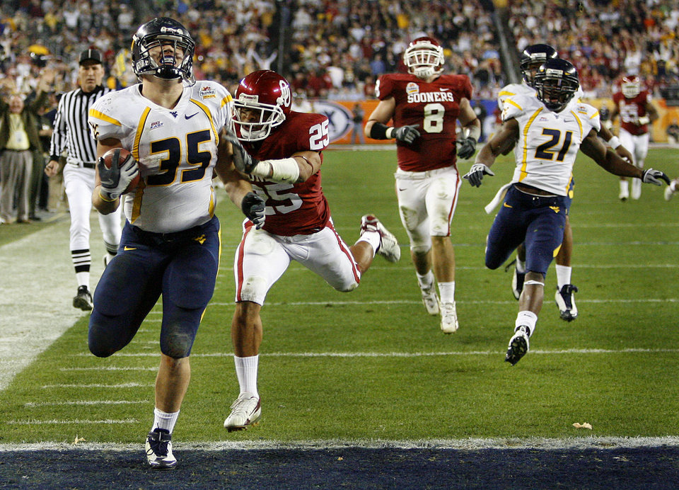 Photo - West Virginia's Owen Schmitt (35) scores a touchdown in front of Oklahoma's D.J. Wolfe (25) during the first half of the Fiesta Bowl college football game between the University of Oklahoma Sooners (OU) and the West Virginia University Mountaineers (WVU) at The University of Phoenix Stadium on Wednesday, Jan. 2, 2008, in Glendale, Ariz. 