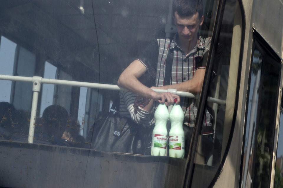 Photo - In this picture taken on Tuesday, May 20, 2014, a man holds bottles of milk while riding on a tram in Donetsk, Ukraine. In the roiling debate over eastern Ukraine, where pro-Russian separatist attacks have turned increasingly bloody, neither the country's richest man nor some of his dirt-poor compatriots have much time for patriotism, ethnic feuding or political parties. (AP Photo/Vadim Ghirda)