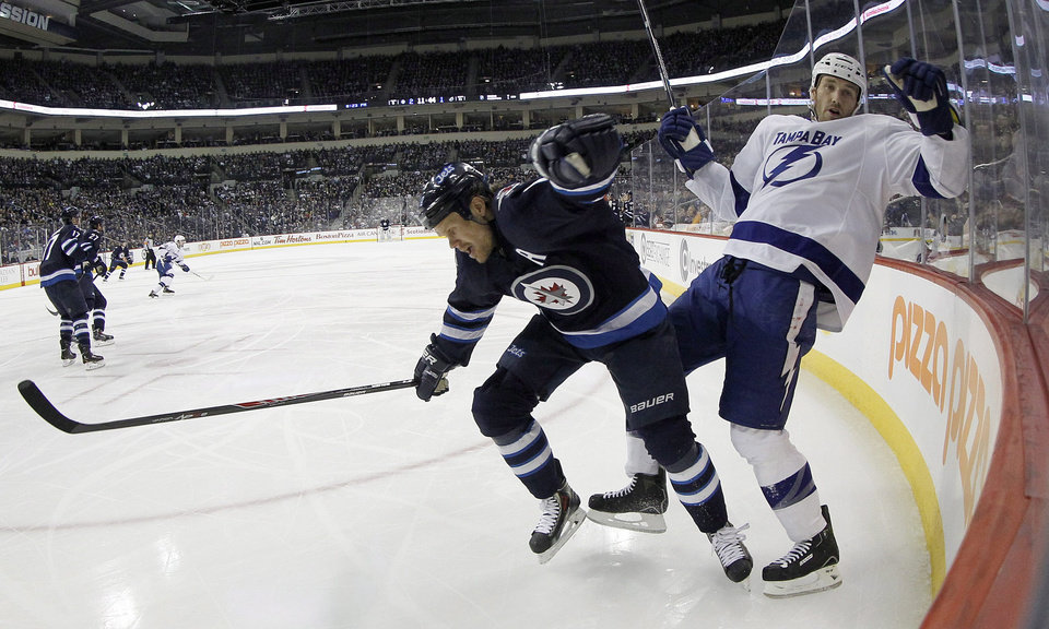 Photo - Winnipeg Jets' Olli Jokinen (12) hits Tampa Bay Lightning's Eric Brewer (2) during the second period of an NHL hockey game Tuesday, Jan. 7, 2014, in Winnipeg, Manitoba. (AP Photo/The Canadian Press, Trevor Hagan)