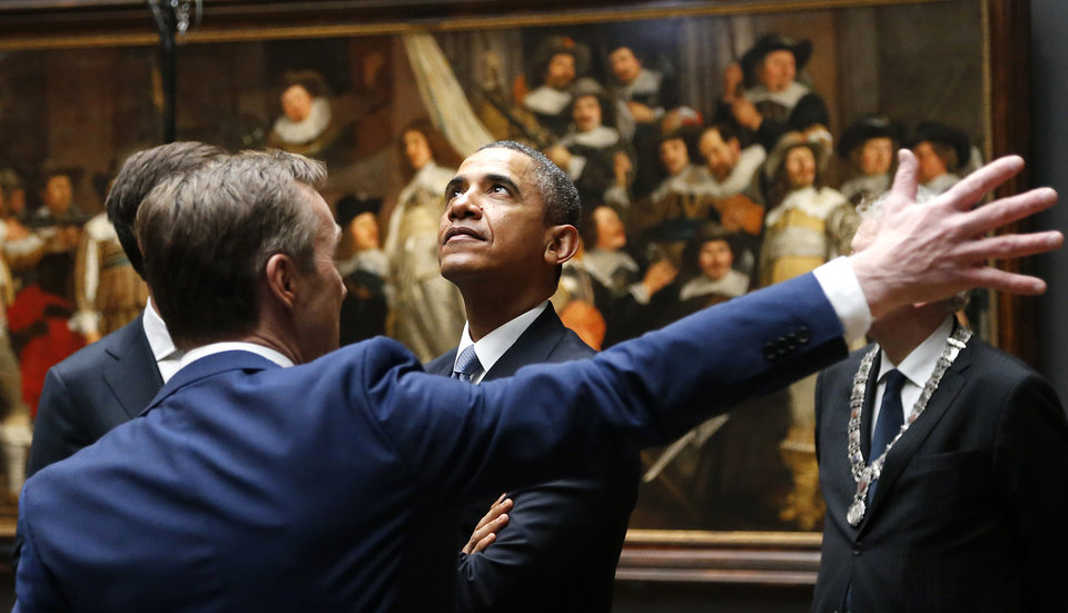 Photo - U.S. President Barack Obama, center, listens to Rijksmuseum director Wim Pijbes, seen from the back, in front of  Dutch master Rembrandt's The Night Watch painting during a visit to the Rijksmuseum in Amsterdam, Netherlands, Monday, March 24, 2014. Obama will attend the two-day Nuclear Security Summit in The Hague. (AP Photo/Frank Augstein)