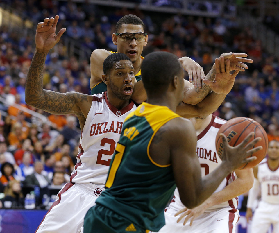 Photo - Baylor's Isaiah Austin (21) passes the ball over Oklahoma's Cameron Clark (21) to Kenny Chery (1) during the Big 12 Tournament college basketball game between the University of Oklahoma and Baylor at the Sprint Center in Kansas City, Mo., Thursday, March 13, 2014. Baylor won 78-73.  Photo by Bryan Terry, The Oklahoman