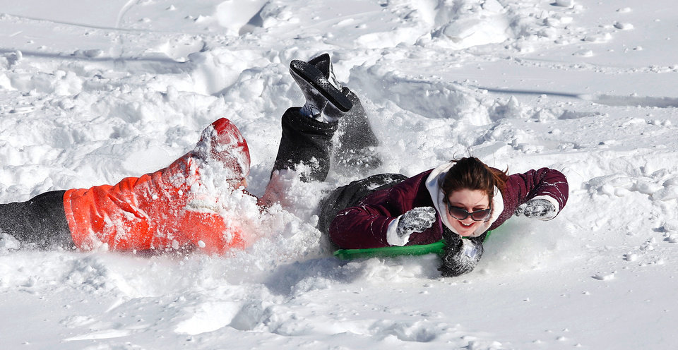 Photo - Kasey Lawrence, 25, and her sister, Samantha Lawrence, 21, braved single digit temperatures Wednesday morning to do a litle sledding on this hill behind Edmond Memorial High School. Central Oklahoma residents began digging out from beneath nearly a foot of snow covering the ground Wednesday, Feb, 2, 2011, after yesterday's winter snowstorm. Photo by Jim Beckel, The Oklahoman