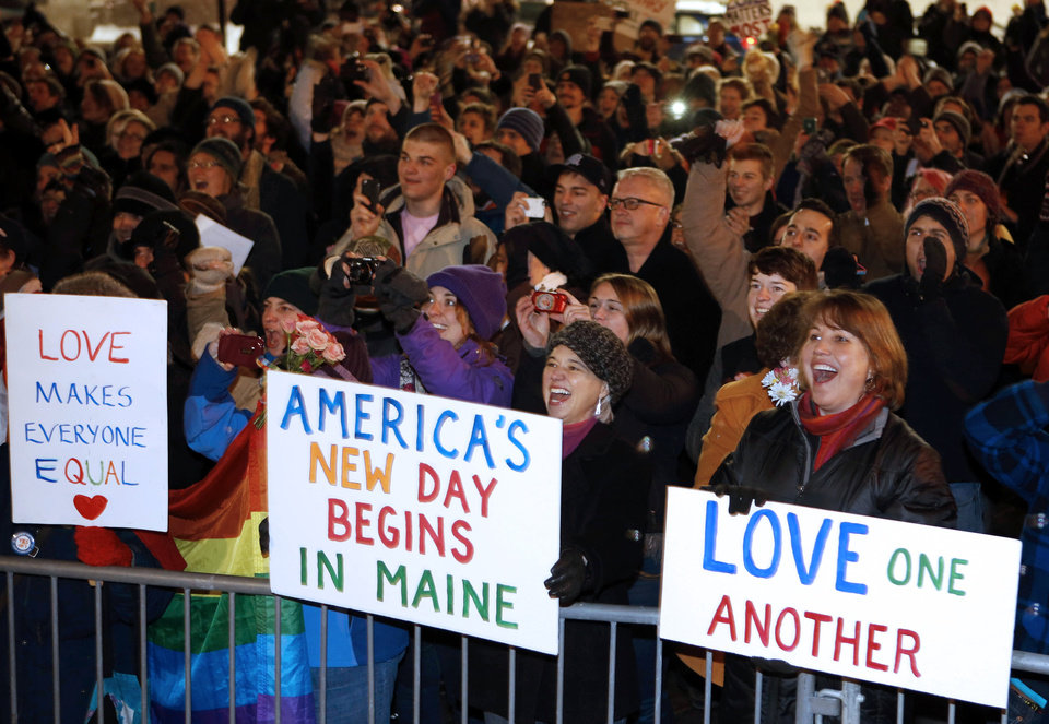 Photo - A crowd cheers at 12:30 a.m. Saturday, Dec. 29, 2012, as the first same-sex couple to be legally married in Maine departs City Hall in Portland, Maine. (AP Photo/Robert F. Bukaty)