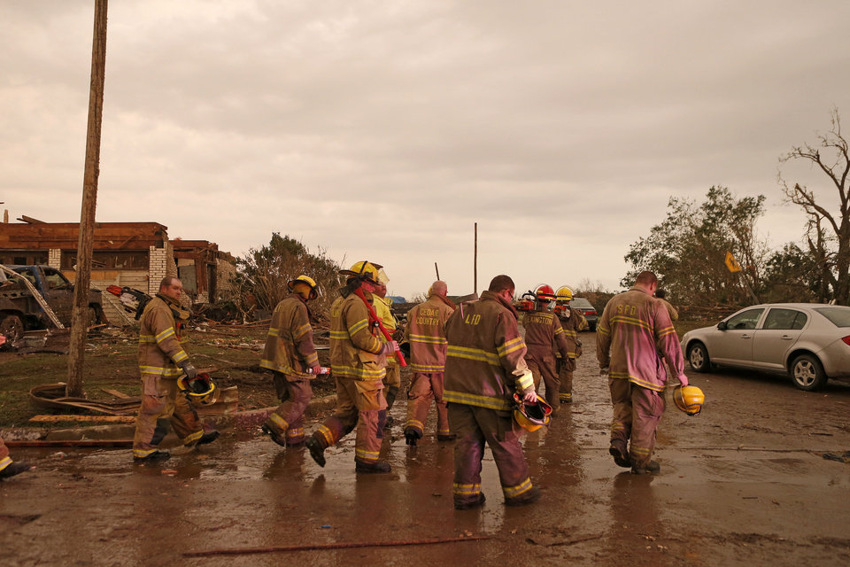 Emergency workers walk through a residential area near Plaza Towers Elementary School in Moore, Okla., after a tornado moved through the area on Monday, May 20, 2013. Photo by Bryan Terry, The Oklahoman