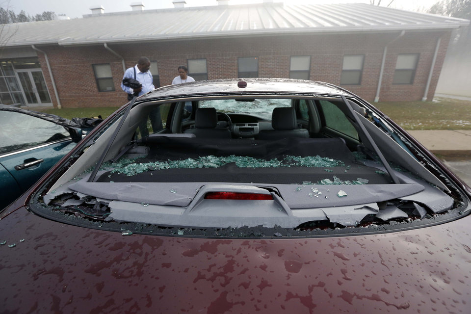 Photo - Andrew Stamps and his wife Valorie prepare to cover their shattered rear window of her 2009 Toyota Avalon in Pearl, Miss., Monday, March 18, 2013, following a hailstorm that hit communities throughout central Mississippi. The National Weather Service in Jackson says there were a few super cells in central Mississippi and reports of hail up to baseball size in Clinton, golf ball and tennis ball sized in Pearl and Brandon and quarter sized in downtown Jackson, Miss. The Mississippi Emergency Management Agency says severe weather has caused damage in at least 10 counties as the storms moved through parts of the state. (AP Photo/Rogelio V. Solis)
