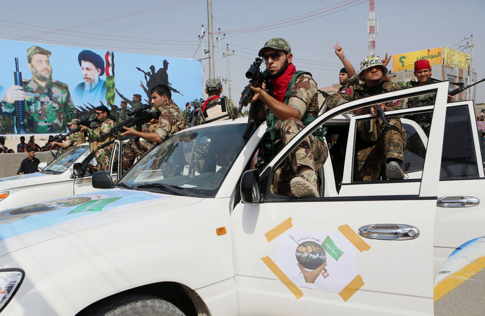 "Volunteers of the newly formed ""Peace Brigades"" participate in a parade in Basra, Iraq's second-largest city, 340 miles (550 kilometers) southeast of Baghdad, Iraq, Saturday, June 21, 2014. The armed group was formed after radical Shiite cleric Muqtatda al-Sadr called to form brigades to protect Shiite holy shrines against possible attacks by Sunni militants. (AP Photo/Nabil Al-Jurani)"